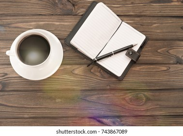 cup of coffee, notebook, pen on a wooden background