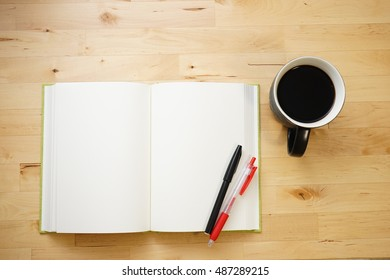 Cup of coffee with notebook and pens on wooden desk
