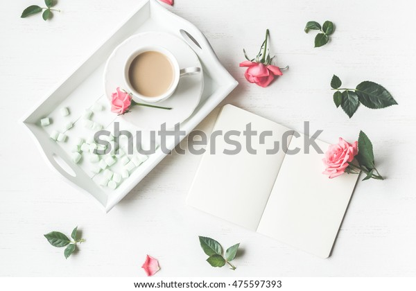 Cup of coffee, notebook and rose flowers. Vintage. Flat lay, top view.