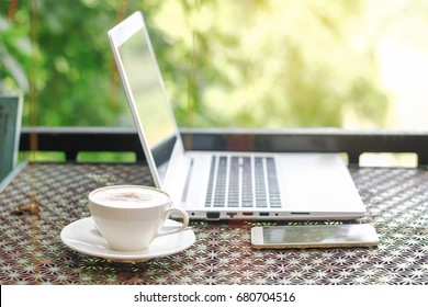 cup of coffee with notebook and smart phone on table at natural greening view in the morning, Happy work place concept
