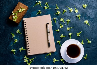 Cup of coffee, notebook, a wooden box and flowers on a dark blue background. The concept of the starry sky and coffee. Flat, top view.