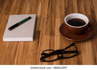 cup of coffee, a notepad and nerd glasses on a wood table