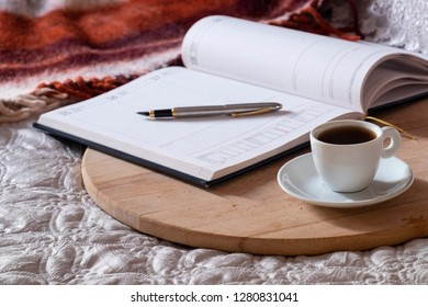 Cup with coffee, notepad, pen on the wooden desk on the bed. With space for text.