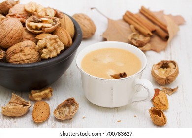 a cup of coffee and nuts on wooden background
