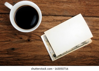 cup of coffee and old paper photo frame on wood background
