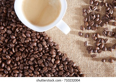 Cup of coffee on a background of coffee beans and a jute bag.