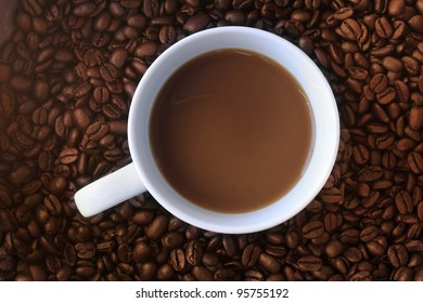 a cup of coffee on a background of dark roast beans