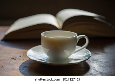 cup of coffee on the background of an open book. A cup on the table in the room.