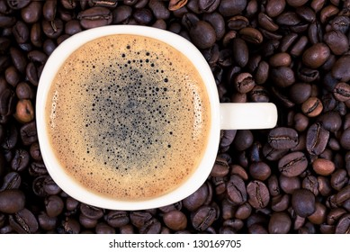 A cup of coffee is on the background of roasted coffee beans