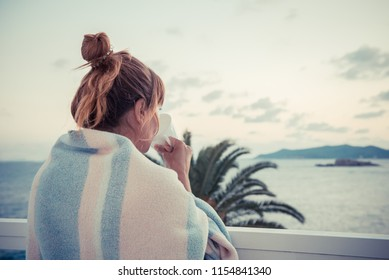 cup of coffee on the balcony. girl on the beach, woman on the sea. girl wrapped in warm blanket woke up in the morning and drinks coffee. girl is standing on balcony with cup of tea