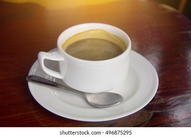 cup of coffee on a beautiful plate on a wooden background. vintage