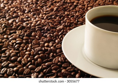 Cup of coffee on a bed of coffee beans