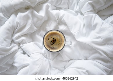 Cup of coffee on bed, top view