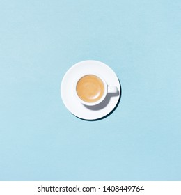 A cup of coffee on blue background. Trendy minimal styled flat lay photography with cappuccino.