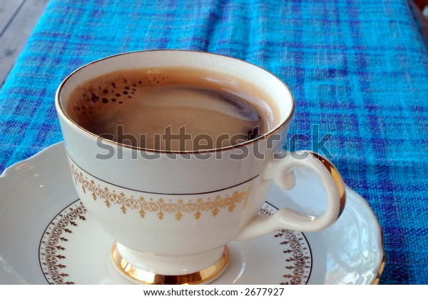 Cup of coffee on blue tablecloth