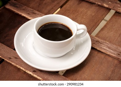 cup of coffee on brown wood table background