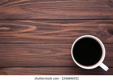 Cup of coffee on brown wooden background. Cup of coffe on wooden table