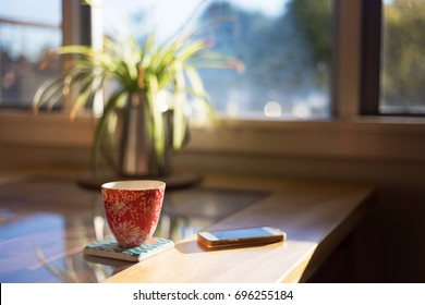 A cup of coffee on a coaster next to smart phone on table with bright morning window light streaming through.