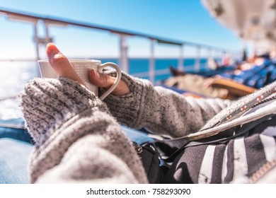 Cup of Coffee on the Cruise Ship Deckchair During Ocean Crossing. Woman Wearing Sweater Holding White Cup of Coffee in Hand.