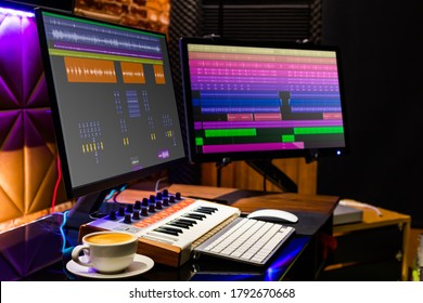 cup of coffee on desk with dual display monitor and midi keyboard for music production