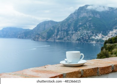 Cup of coffee on edge at sea view. Horizontal view with white cup with tea or coffee on old stand in front of sea, close up.