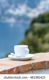 Cup of coffee on edge at sea view. Vertical view with white cup with tea or coffee on old stand in front of sea, close up.