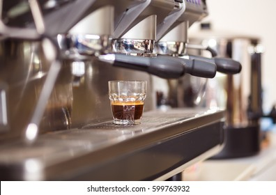 A cup of coffee is on the espresso machine - Shutterstock ID 599763932
