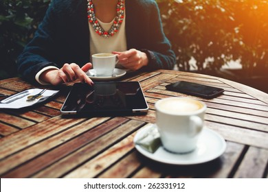 Cup of coffee on the foreground with elegant woman using busy touch screen tablet and drinking cappuccino at the coffee shop, bill check and mobile phone near, flare sun light
