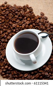 Cup of coffee on coffee grains. A hot drink