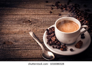 A cup of coffee on old wooden table with some beans a spoon and a stick of cinnamon