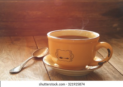 cup of coffee on old wooden table. morning workspace, coffee break .retro filtered image and selective focus