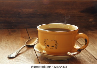 cup of coffee on old wooden table. morning workspace, coffee break . selective focus