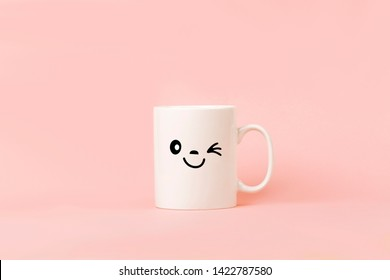 Cup of coffee on pink background with happy smile face on mug.