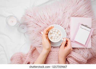 A cup of coffee on a pink pillow with notebook and a blanket on the bed. Flat lay, top view