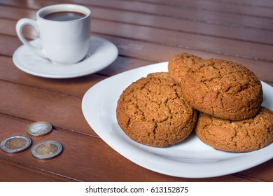 A cup of coffee on a plate of biscuits and coins on a wooden table