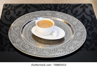 A cup of coffee on a silver tray.