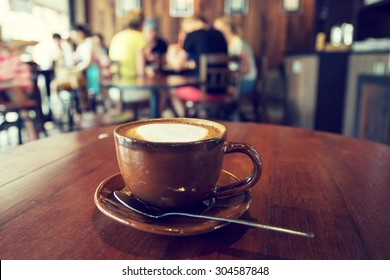 Cup of coffee on table in cafe, vintage or retro color effect- shallow depth of field