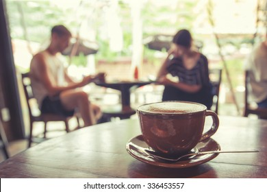 Cup of coffee on table in cafe with people retro instagram effect - shallow depth of field