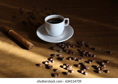 A cup of coffee on the table and a cigar.
