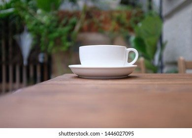 a cup of coffee on the table in the coffeshop outside