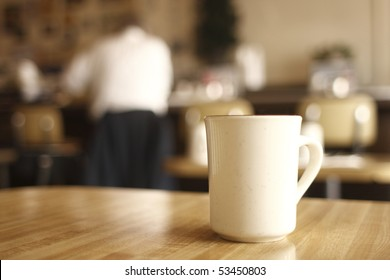 A cup of coffee on the table at a diner.