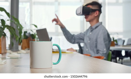 Cup of coffee on the table, man using 3d vr glasses at work on the background