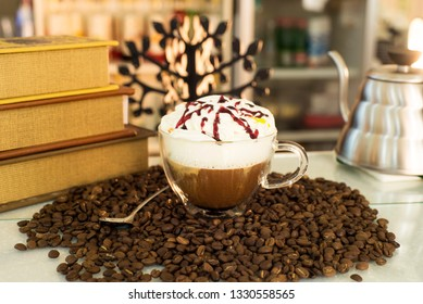 cup of coffee on the table next to the books in the coffee beans