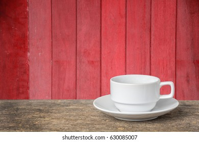Cup of coffee on the table old with wooden red background.