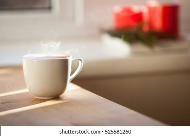 A cup of coffee on table and red blurred  candles on background