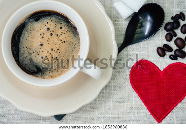 Cup of coffee on tablecloth with red heart, seen from above
