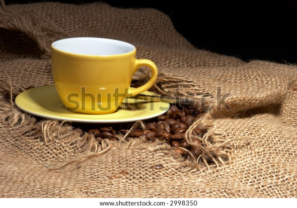 cup of coffee on tattered burlap sack and coffee beans