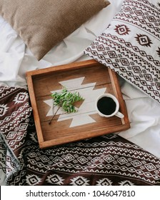 cup of coffee on a tray with a green branch in the bedroom on the bed