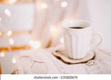 Cup of coffee on the warm beige knitted sweater background. Autumn and winter, leisure concept. Cozy, comfy, soft. Flat lay