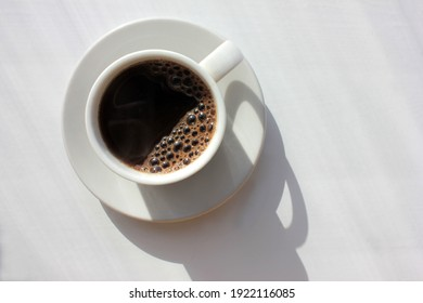 Cup of coffee on white background. Top view, copy space. Morning espresso on table. Hard light, deep shadow. Selective focus